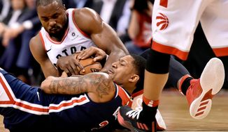 Toronto Raptors forward Serge Ibaka (9) wrestles for control of the ball with Washington Wizards guard Bradley Beal during the second half of Game 2 of an NBA basketball first-round playoff series Tuesday, April 17, 2018, in Toronto. (Nathan Denette/The Canadian Press via AP)