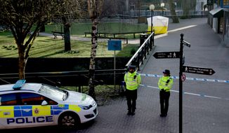 """FILE - In this Wednesday, March 7, 2018 file photo, police officers guard a cordon around a police tent covering the the spot where former Russian double agent Sergei Skripal and his daughter were found critically ill Sunday following exposure to an """"unknown substance"""" in Salisbury, England. British officials said Tuesday April 17, 2018, the nerve agent used to poison former Russian spy Sergei Skripal and his daughter was delivered in liquid form, and it will take months to remove all traces of the toxin. (AP Photo/Matt Dunham, File)"""