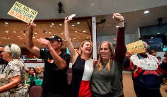 In this March 27, 2018, file photo, David Hernandez, left, Genevieve Peters, center, and Jennifer Martinez celebrate after the Orange County Board of Supervisors voted to join the U.S. Department of Justice lawsuit against the State of California's sanctuary cities law (SB54) during their meeting in Santa Ana, Calif. Leaders of California's second-largest county voted Tuesday, April 17, 2018, to officially support the Trump administration's lawsuit against the state's so-called sanctuary law that limits police cooperation with federal immigration agents. (Jeff Gritchen/The Orange County Register via AP, File)