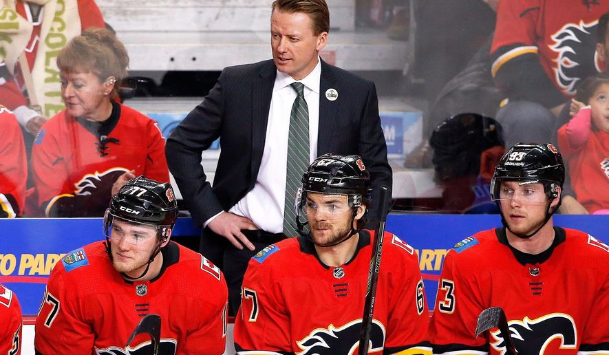 FILE - In this Saturday, April 7, 2018, file photo, Calgary Flames coach Glen Gulutzan, top, watches during the team's NHL hockey game against the Vegas Golden Knights in Calgary, Alberta. The Flames fired Gulutzan on Tuesday, April 17, 2018, after two years with the club. Assistant coaches Dave Cameron and Paul Jerrard were also relieved of their duties. (Larry MacDougal/The Canadian Press via AP, File)
