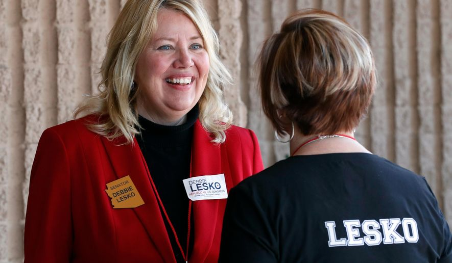 Arizona State Rep. and U.S. Representative candidate Debbie Lesko speaks with a constituent during the meeting of the state committee of the Arizona Republican Party in Phoenix. The sprawling suburbs west of Phoenix may put a brake on Democratic optimism following surprising special election wins in places like Alabama, Pennsylvania and other GOP strongholds. (AP Photo/Matt York, File)