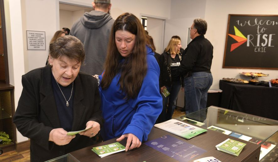 Diane Walters, left, and her caregiver Tasha Zirkle look over free literature during an open house in Erie, Pa., Monday, April 16, 2018, at the region's first medical marijuana dispensary that will be open April 18, for patients with state-issued medical marijuana identification cards. (Christopher Millette/Erie Times-News via AP)