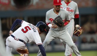 Philadelphia Phillies shortstop J.P. Crawford (2) can't turn a double play after forcing out Atlanta Braves' Freddie Freeman (5) at second base on a Nick Markakis ground ball in the first inning of a baseball game Tuesday, April 17, 2018, in Atlanta. (AP Photo/John Bazemore)