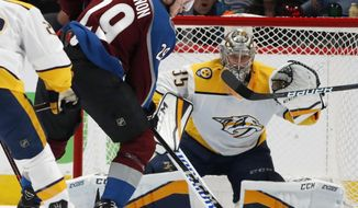 Colorado Avalanche center Nathan MacKinnon, front, fires a shot at Nashville Predators goaltender Pekka Rinne for a goal in the second period of Game 3 of an NHL hockey first-round playoff series Monday, April 16, 2018, in Denver. (AP Photo/David Zalubowski)