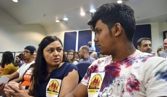 Nora Hernandez, left, of the immigrant advocacy group New Mexico Dream Team, speaks with Javier Solis, a local high school senior, ahead of a City Council meeting on whether to bolster immigrant friendly policies in Albuquerque, New Mexico, on Monday, April 17, 2018. The Albuquerque City Council voted to enact immigrant friendly policies at the meeting, including one that that would bar federal immigration agents from prisoner transport centers without a warrant, and another that would prevent city workers from asking about people's immigration status. (AP Photo/Mary Hudetz)