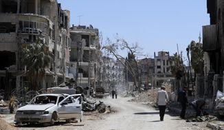 """Syrians walk through destruction in the town of Douma, the site of a suspected chemical weapons attack, near Damascus, Syria, Monday, April 16, 2018. Faisal Mekdad, Syria's deputy foreign minister, said on Monday that his country is """"fully ready"""" to cooperate with the fact-finding mission from the Organization for the Prohibition of Chemical Weapons that's in Syria to investigate the alleged chemical attack that triggered U.S.-led airstrikes. (AP Photo/Hassan Ammar)"""