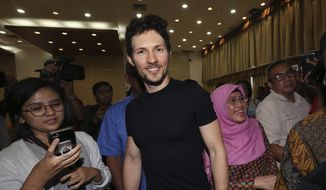 In this Aug. 1, 2017, file photo, Telegram co-founder Pavel Durov, center, smiles following his meeting with Indonesian Communication and Information Minister Rudiantara in Jakarta, Indonesia. (AP Photo/Tatan Syuflana, File)
