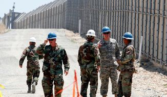 """FILE - In this June 21, 2006 file photo, members of the California National Guard work next to the U.S.-Mexico border fence near the San Ysidro Port of Entry in San Diego. President Donald Trump slammed California Gov. Jerry Brown's posture on sending National Guard troops to the Mexican border Tuesday, April 17, 2018, even as Brown said he was nearing agreement on joining the president's mission and that his troops were """"chomping at the bit ready to go."""" (AP Photo/Denis Poroy, File)"""
