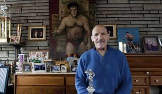"FILE - In this March 27, 2013, file photo, Bruno Sammartino sits in front of pictures, panitings and trophies highlighting his storied career as a wrestler and weightlifter, at his home in his North Hills, Pa., home. Bruno Sammartino, professional wrestling's ""Living Legend"" and one of its longest-reigning champions, has died. Sammartino was 82.  Family friend and former wrestling announcer Christoper Crusie saids Sammartino died Wednesday morning, April 18, 2018, and had been hospitalized for two months. (Andrew Russell/Pittsburgh Tribune-Review via AP, File) **FILE*"