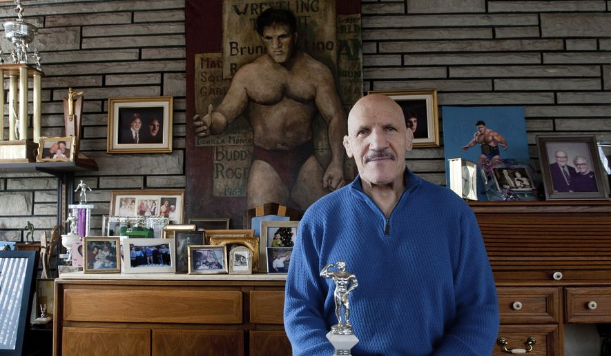 """FILE - In this March 27, 2013, file photo, Bruno Sammartino sits in front of pictures, panitings and trophies highlighting his storied career as a wrestler and weightlifter, at his home in his North Hills, Pa., home. Bruno Sammartino, professional wrestling's """"Living Legend"""" and one of its longest-reigning champions, has died. Sammartino was 82.  Family friend and former wrestling announcer Christoper Crusie saids Sammartino died Wednesday morning, April 18, 2018, and had been hospitalized for two months. (Andrew Russell/Pittsburgh Tribune-Review via AP, File) **FILE*"""