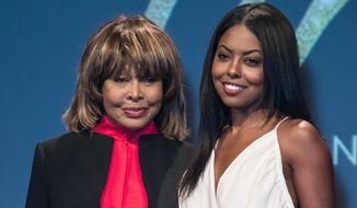 FILE - In this Tuesday, Oct. 17, 2017 file photo, musician Tina Turner, left, poses for photographers with actress Adrienne Warren, who plays Tina Turner, during a photo call to promote the launch of the musical 'Tina', in London. British theater critics are praising a stage musical about the life of Tina Turner, and it also has the approval of the star herself. (Photo by Vianney Le Caer/Invision/AP, File)