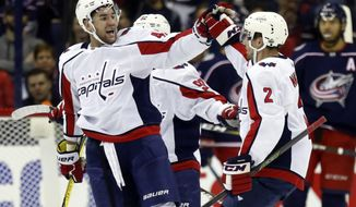 Washington Capitals forward Tom Wilson, left, celebrates with teammate defenseman Matt Niskanen after Niskanen's goal against the Columbus Blue Jackets during the second period in Game 3 of an NHL first-round hockey playoff series in Columbus, Ohio, Tuesday, April 17, 2018. (AP Photo/Paul Vernon)