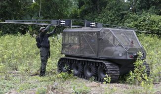 An police officer calibrates the sprinkles of a tactical vehicle use to spray herbicides before testing it on a coca field in Tumaco, southern Colombia, Wednesday, April, 18, 2018. According to U.S. officials, coca production in Colombia has gone up 50% in each of the last two years, with about 247,000 acres now under cultivation, and with each acre cultivated more productive than before counter narcotics officials are testing new ways to eradicate including the use of drones and tactical vehicles to spray. (AP Photo/Fernando Vergara)