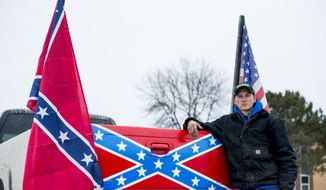 """Cameron Meyers poses outside Bay City Western High School with his truck on Wednesday, April 18 2018, in Auburn, Mich. Meyers claims his Confederate flag was torn from his truck last Thursday, April 12, by a fellow Western student and his calls for the administration to discipline that student went unanswered. """"They shut me down,"""" Myers said. """"They should be punished for destruction of property."""" (Jacob Hamilton/The Bay City Times via AP)"""