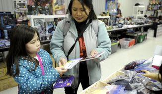 In this photo taken April 8, 2018, Theresa Seminara, 7, picks out books with her mother, Theresa, during the Buster-Con Toy Show at the Union Club in Kenosha, Wis. (Sean Krajacic/The Kenosha News via AP)