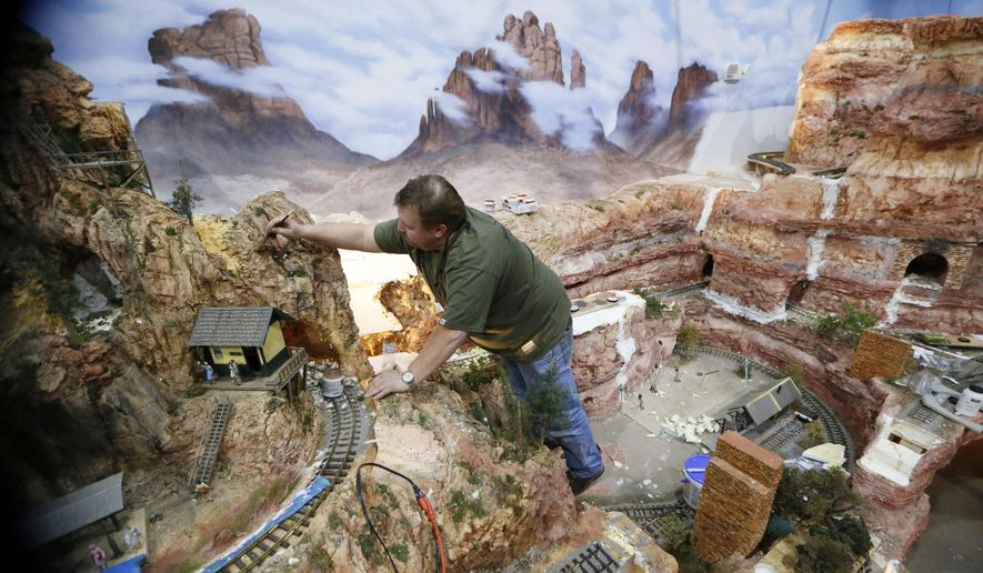 In this April 9, 2018 photo, Andy Wartman paints texture on one of the mountains in the Museum of the American Railroad at Frisco Discovery Center in Frisco, Texas. A grand opening in June is planned for the Museum of the American Railroad's new exhibit, aptly named TrainTopia. (Nathan Hunsinger/The Dallas Morning News via AP)