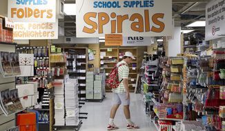 In a Oct. 10, 2013 photo, Ben Salinaro, a freshman Radio, Television and Film major, looks for supplies along with the textbooks at the Co-Op in Austin, Texas. The University Co-Op on Guadalupe Street across from the University of Texas campus has long been a fixture of college life offering clothing and fan gear, to textbooks and memorabilia. (Ralph Barrera/Austin American-Statesman via AP)