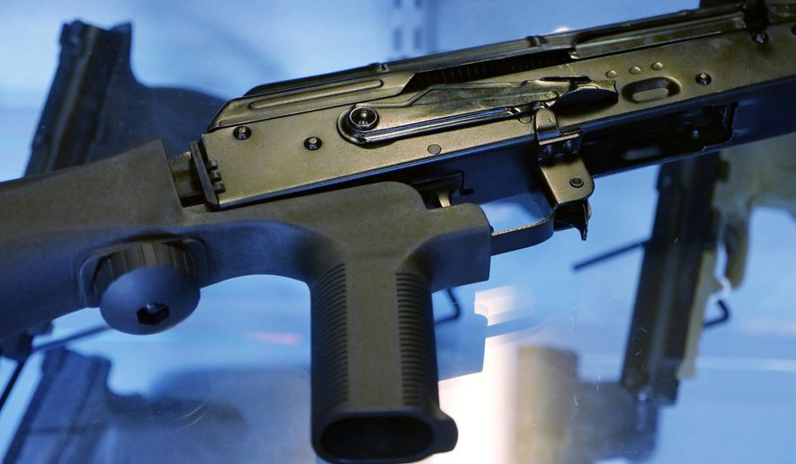 "FILE - In this Oct. 4, 2017, file photo, a device called a ""bump stock"" is attached to a semi-automatic rifle at the Gun Vault store and shooting range in South Jordan, Utah. Hawaii lawmakers are discussing two bills that would tighten the state's already strict gun regulations. (AP Photo/Rick Bowmer, File)"