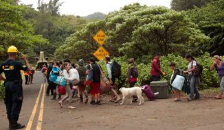 Evacuees prepare to board a U.S. Army Chinook on Tuesday, April 17, 2018 in Wainiha, Kauai. Hundreds of people have been airlifted out of dangerous floodwaters on the Hawaiian island of Kauai, but authorities said Tuesday that others are still stranded at evacuation centers. (Jamm Aquino/Honolulu Star-Advertiser via AP)