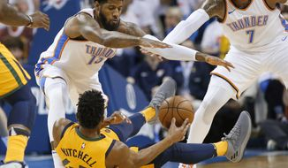 Oklahoma City Thunder forwards Paul George (13) and Carmelo Anthony (7) try to keep Utah Jazz guard Donovan Mitchell (45) from passing the ball during the first half of Game 2 of an NBA basketball first-round playoff series in Oklahoma City, Wednesday, April 18, 2018. (AP Photo/Sue Ogrocki)