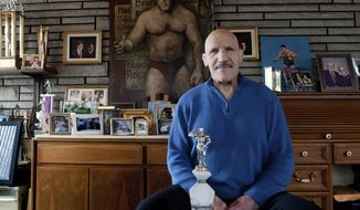 "FILE - In this March 27, 2013, file photo, Bruno Sammartino sits in front of pictures, panitings and trophies highlighting his storied career as a wrestler and weightlifter, at his home in his North Hills, Pa., home. Bruno Sammartino, professional wrestling's ""Living Legend"" and one of its longest-reigning champions, has died. Sammartino was 82. Family friend and former wrestling announcer Christoper Crusie saids Sammartino died Wednesday morning, April 18, 2018, and had been hospitalized for two months. (Andrew Russell/Pittsburgh Tribune-Review via AP, File)"