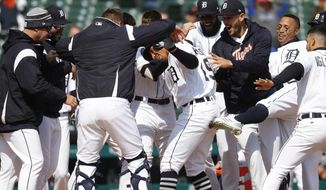 Detroit Tigers' Dixon Machado, center, is congratulated for his walk off solo home run in the ninth inning of a baseball game against the Baltimore Orioles in Detroit, Wednesday, April 18, 2018. Detroit won 6-5. (AP Photo/Paul Sancya)