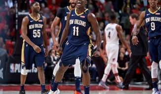 New Orleans Pelicans guard Jrue Holiday, center, forward E'Twaun Moore, left, forward Anthony Davis, second from left, and guard Rajon Rondo, right, celebrate during the second half of Game 2 against the Portland Trail Blazers in an NBA basketball first-round playoff series Tuesday, April 17, 2018, in Portland, Ore. The Pelicans won 111-102. (AP Photo/Craig Mitchelldyer)