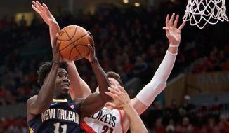New Orleans Pelicans guard Jrue Holiday, left, shoots next to Portland Trail Blazers center Jusuf Nurkic during the first half of Game 2 of an NBA basketball first-round playoff series Tuesday, April 17, 2018, in Portland, Ore. (AP Photo/Craig Mitchelldyer)