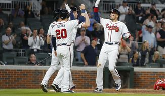 Atlanta Braves' Ryan Flaherty, right, celebrates with teammates, including Preston Tucker (20) and Danby Swanson, back left, after hitting a three-run home run in the fifth inning of a baseball game against the Philadelphia Phillies, Wednesday, April 18, 2018, in Atlanta. (AP Photo/Todd Kirkland)
