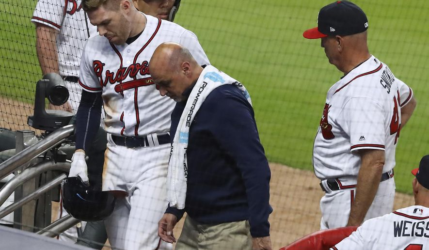 Atlanta Braves' Freddie Freeman leaves the field with a trainer as manager Brian Snitker watches after Freeman was hit by a pitch by Philadelphia Phillies' Hoby Milner during the eighth inning of a baseball game Wednesday, April 18, 2018, in Atlanta. (Curtis Compton/Atlanta Journal-Constitution via AP)