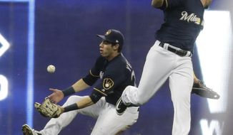 Milwaukee Brewers' Hernan Perez watches as Christian Yelich catches a ball hit by Cincinnati Reds' Alex Blandino during the second inning of a baseball game Wednesday, April 18, 2018, in Milwaukee. (AP Photo/Morry Gash)