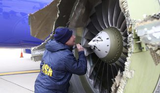 "In this Tuesday, April 17, 2018, photo, a National Transportation Safety Board investigator examines damage to the engine of the Southwest Airlines plane that made an emergency landing at Philadelphia International Airport in Philadelphia. A preliminary examination of the blown jet engine of the Southwest Airlines plane that set off a terrifying chain of events and left a businesswoman hanging half outside a shattered window showed evidence of ""metal fatigue,"" according to the National Transportation Safety Board. (NTSB via AP)"