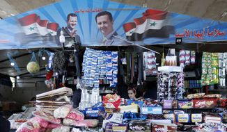 """A girl shops at a kiosk in Damascus, Syria, Tuesday, April 17, 2018. The Arabic on the right reads, """"Regards Assad, God protect you Assad."""" (AP Photo/Hassan Ammar)"""