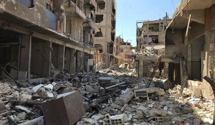 """Rubble fills a street in Douma, the site of a suspected chemical weapons attack, near Damascus, Syria, Monday, April 16, 2018. Faisal Mekdad, Syria's deputy foreign minister, said on Monday that his country is """"fully ready"""" to cooperate with the fact-finding mission from the Organization for the Prohibition of Chemical Weapons that's in Syria to investigate the alleged chemical attack that triggered U.S.-led airstrikes. (AP Photo/Hassan Ammar)"""