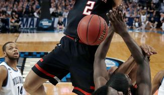 FILE - In this March 25, 2018, file photo, Texas Tech's Zhaire Smith, top, dunks against Villanova during the second half of an NCAA men's college basketball tournament regional final in Boston. Texas Tech standout freshman guard Smith says he is signing with an agent and will be available in the NBA draft. Smith said in a Twitter post that he is signing with Roc Nation and forgoing the rest of his collegiate career. (AP Photo/Charles Krupa, File)