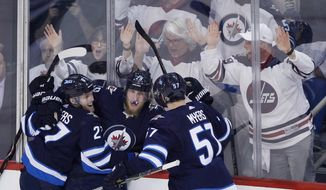 Winnipeg Jets' Nikolaj Ehlers (27), Patrik Laine (29) and Tyler Myers (57) celebrate Laine's goal against the Minnesota Wild during the third period of Game 1 in an NHL hockey first-round playoff series Wednesday, April 11, 2018, in Winnipeg, Manitoba. (John Woods/The Canadian Press via AP) **FILE**