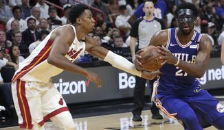 Philadelphia 76ers' Joel Embiid,, right, drives to the basket as Miami Heat's Hassan Whiteside, left, defends during the first half of Game 3 of a first-round NBA basketball playoff series Thursday, April 19, 2018, in Miami. (AP Photo/Lynne Sladky)