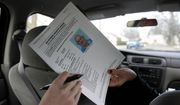 In this Thursday, Jan. 26, 2012 photo, a sex offender registry board image of designated Level 3 sex offender Charles D. Clark Jr., is passed from Detective Tracy Duda, right, to a member of the media in a car in Springfield, Mass. (AP Photo/Steven Senne)