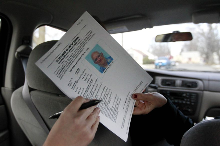 In this Thursday, Jan. 26, 2012, file photo, a sex offender registry board image of designated Level 3 sex offender Charles D. Clark Jr., is passed from Detective Tracy Duda, right, to a member of the media in a car in Springfield, Mass. (AP Photo/Steven Senne) ** FILE **