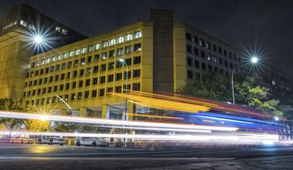 FILE - In this Nov. 1, 2017, file photo, traffic along Pennsylvania Avenue in Washington streaks past the Federal Bureau of Investigation headquarters building. In the two weeks since the #Releasethememo hashtag first sprouted on Twitter, a secret congressional report on the Russia investigation has gone from an obscure, classified document to a bitter point of conflict between not only Democrats and Republicans but also the White House and the FBI. (AP Photo/J. David Ake)