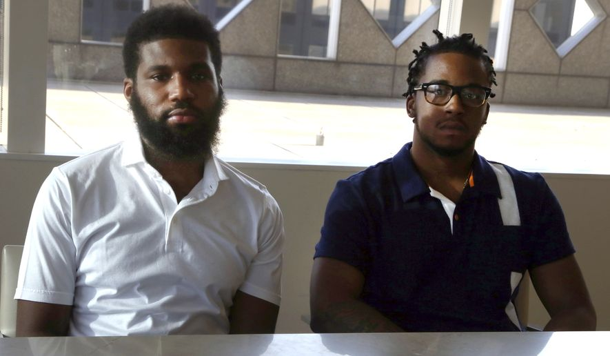 Rashon Nelson, left, and Donte Robinson, right, both 23, sit in their attorney's conference room as they pose for a portrait following an interview with The Associated Press Wednesday April 18, 2018 in Philadelphia. Their arrests at a local Starbucks quickly became a viral video and galvanized people around the country who saw the incident as modern-day racism. In the week since, Nelson and Robinson have met with Starbucks CEO Kevin Johnson and are pushing for lasting changes to ensure that what happened to them doesn't happen to future patrons. They are also still processing what it means to have had an everyday encounter escalate into a police confrontation. (AP Photo/Jacqueline Larma)