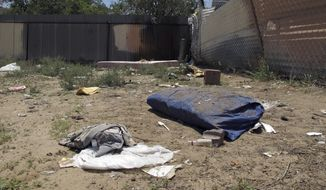 FILE--In this Monday, July 21, 2014, file photo, bedding, clothing and broken glass litter a homeless encampment in Albuquerque, N. M., where authorities say three teenagers fatally beat two homeless Navajo men in a crime so alarming it led to the creation of a city task force on Native American homelessness. The recent March 2018 killing in Albuquerque of another homeless man who also was from the Navajo Nation is again exposing the heightened dangers many say Native Americans coping with homelessness often face. (AP Photo/Jeri Clausing, file)