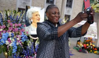 Rhea Brown Lawson, director of the Houston Public Library, takes a photo in front of a memorial for former first lady Barbara Bush, Thursday, April 19, 2018, in Houston. (AP Photo/Evan Vucci)