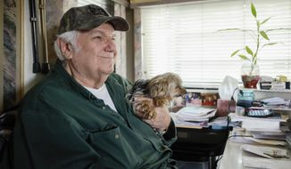In this April 4, 2018 photo, Dan Bell sits with his dog while talking about his RV at Leah's Landing in Nampa, Idaho. (Chris Bronson /The Idaho Press-Tribune via AP)