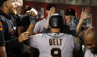 San Francisco Giants' Brandon Belt (9) celebrates his two-run home run against the Arizona Diamondbacks with Hunter Pence, left, and other teammates during the 10th inning of a baseball game Wednesday, April 18, 2018, in Phoenix. (AP Photo/Ross D. Franklin)
