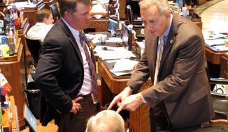 State Reps. Stephen Dwight, left, R-Lake Charles, left, and Mark Abraham, R-Lake Charles, speak with Rep. Mike Danahay, D-Sulphur, seated, on the House floor, Thursday, April 19, 2018, in Baton Rouge, La. The House debated a $27 billion state operating budget Thursday. (AP Photo/Melinda Deslatte)