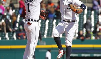 Detroit Tigers' Jose Iglesias (1) and Leonys Martin (12) celebrate their 13-8 win over the Baltimore Orioles after a baseball game in Detroit, Thursday, April 19, 2018. (AP Photo/Paul Sancya)