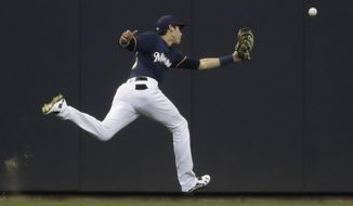 Milwaukee Brewers' Christian Yelich can't catch a ball hit by Cincinnati Reds' Jesse Winker during the first inning of a baseball game Wednesday, April 18, 2018, in Milwaukee. (AP Photo/Morry Gash)