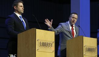 Republican primary senatorial candidate Corey Stewart, right, gestures as Del. Nick Freitas listens during a debate at Liberty University in Lynchburg, Va., Thursday, April 19, 2018. (AP Photo/Steve Helber)