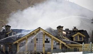 Firefighters work to extinguish a blaze that heavily damaged the Warm Springs Lodge Thursday, April 19, 2018, after a fire broke out late Wednesday at the famed lodge at the base of one of the nation's premier ski destinations in Sun Valley, Idaho. There were no immediate reports of injuries, no damage estimate and no immediate word on the cause. The lodge closed for the season last Sunday and was not open to the public when the fire started. (Jason Kindred/Idaho Mountain Express via AP)